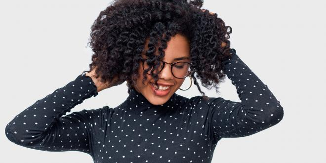 African American female smiling broadly with her hands in her beautiful, healthy hair.